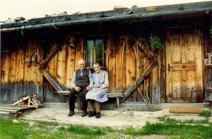 elderly couple sitting on a bench in front of a cabin